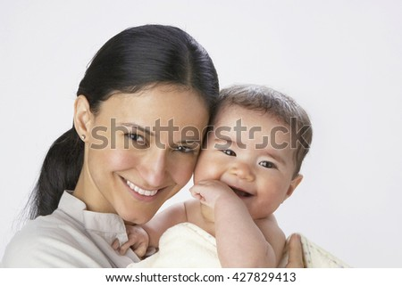 Adorable baby with his mother in studio shot - stock photo