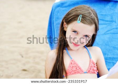Adorable beautiful brunette kid  girl having fun on the beach - stock photo