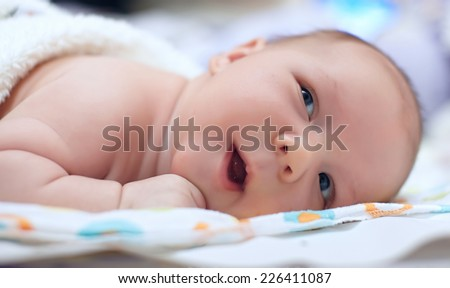 Adorable beautiful newborn baby boy looking up - stock photo