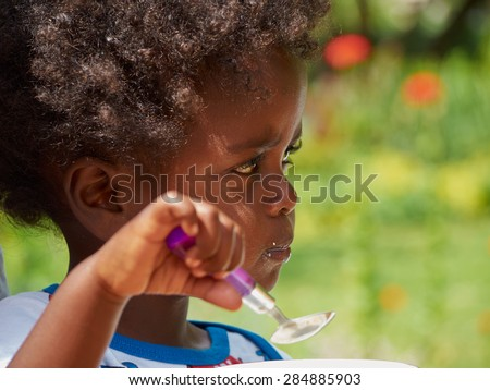 Adorable black African baby eating with food full face - stock photo