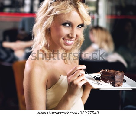 Adorable blond beauty eating a chocolate cake - stock photo