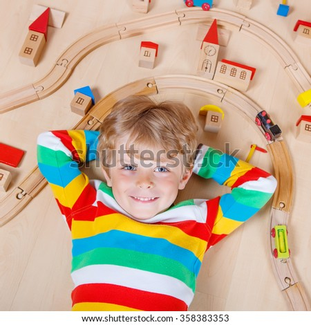 Adorable blond child  playing wooden trains and roalroad indoor. Active kid boy wearing colorful shirt and having fun with building and creating. - stock photo