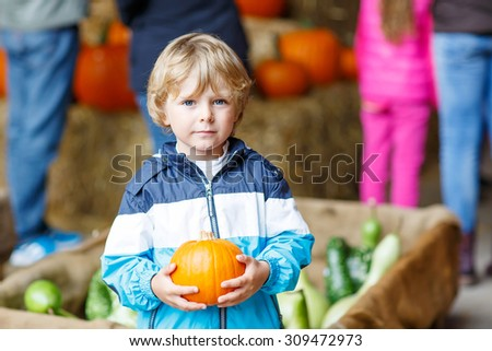 Adorable blond kid boy holding orange pumpkin on halloween or thanksgiving harvest festival or patch, outdoors - stock photo