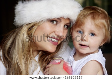 Adorable blond little girl with blue eyes and mother with furry santa hat. - stock photo