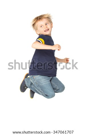 Adorable blond smiling boy jumping and raises his hands up.  Isolated on white background. Shooting in the studio - stock photo