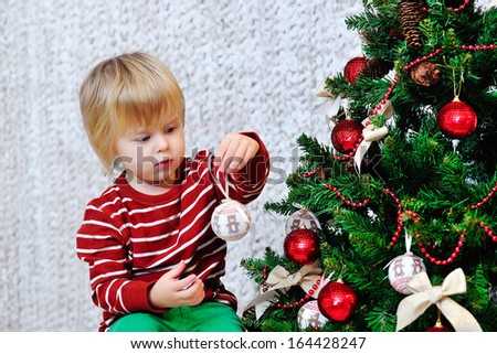 Adorable blond toddler decorating Christmas tree - stock photo