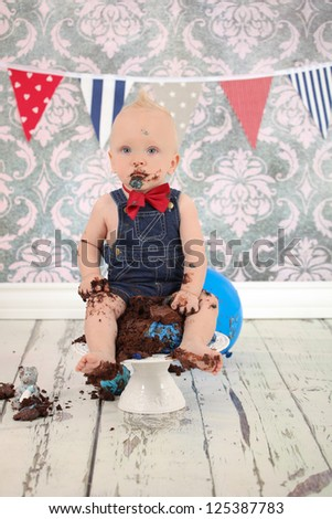 Adorable blonde haired boy with face covered in blue butter icing and sticky fingers eating cake at his birthday party - stock photo