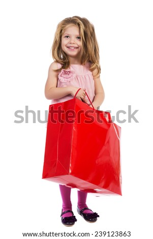 Adorable blonde little girl with pink dress holding a shopping bag isolated over white background - stock photo
