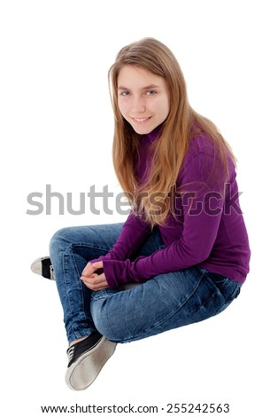 Adorable blonde teenager looking at camera sitting on floor isolated on a white background - stock photo