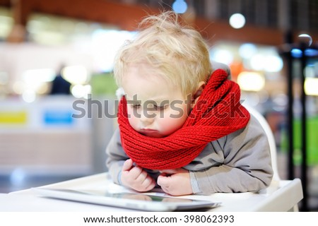 Adorable blonde toddler boy playing with a digital tablet indoors    - stock photo