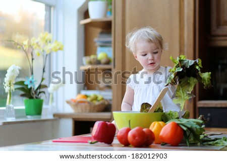 Adorable blonde toddler girl in beautiful white dress mixing vegetables in the bowl preparing healthy salad sitting on the table in sunny kitchen with big garden view window - stock photo