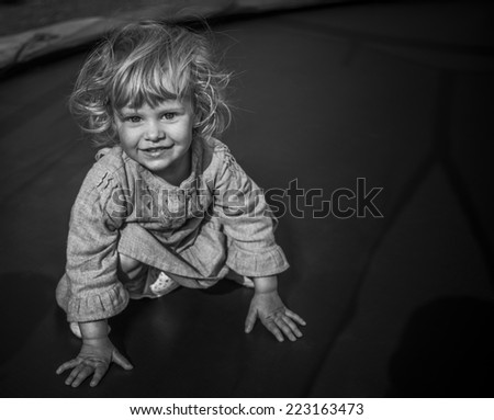 adorable blonde  toddler girl sitting on a trampoline in black and white - stock photo