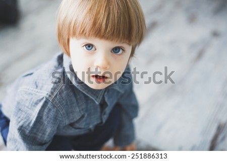Adorable blue eyed baby boy sitting on blue-grey floor and looking into the camera - stock photo