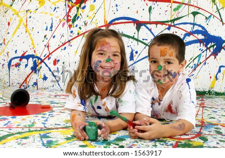 Adorable boy and girl covered in paint lying on splattered paint background - stock photo