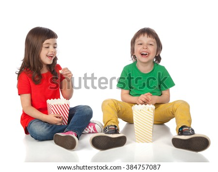 Adorable boy and girl having great time eating popcorn, isolated on white - stock photo