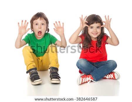 Adorable boy and girl having great time making faces, isolated on white - stock photo