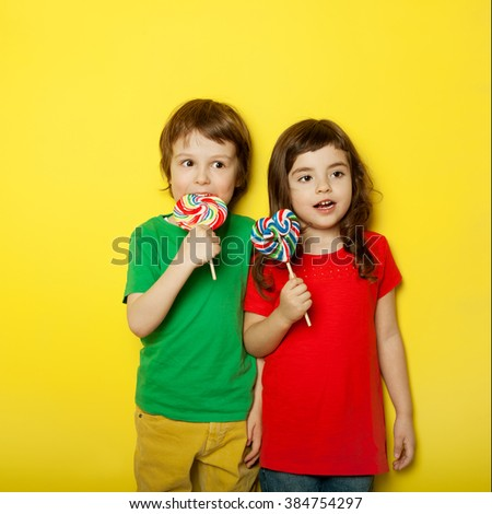 Adorable boy and girl having great time while licking lollipops, on red and yellow background - stock photo