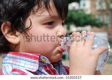Adorable boy drinking water - stock photo
