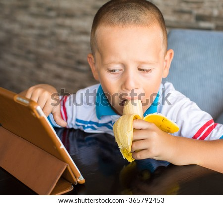 Adorable boy, eating his banana, while watching movie on tablet - stock photo