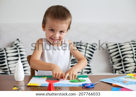 Adorable boy, making decoration picture from colorful paper at home - stock photo