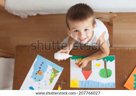 Adorable boy, making decoration picture from colorful paper at home, looked from above - stock photo