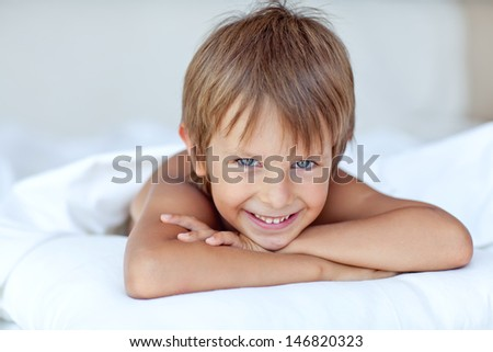 adorable boy on a bed  - stock photo