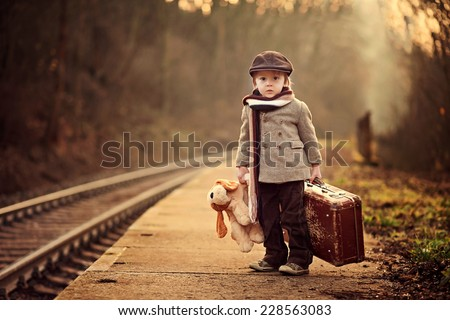 Adorable boy on a railway station, waiting for the train with suitcase and teddy bear - stock photo