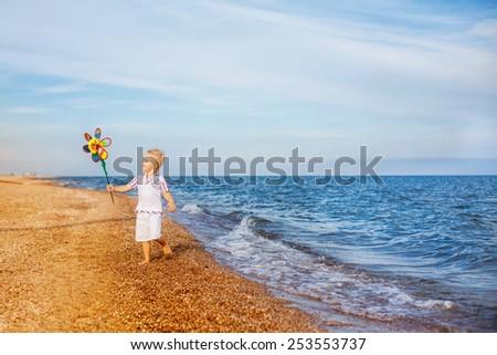 adorable boy running along the beach - stock photo