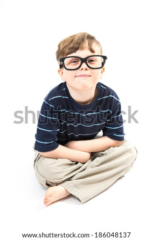 Adorable boy sits cross legged with silly glasses on, on white background - stock photo