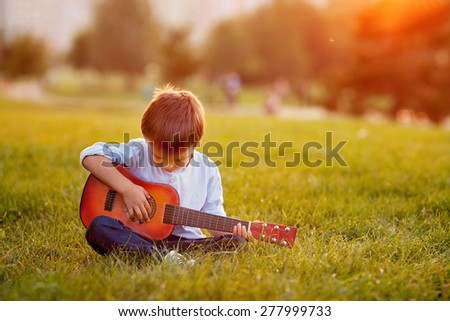 Adorable boy with guitar, sitting on the grass on sunset - stock photo