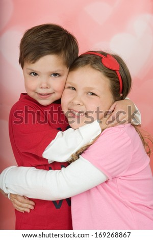 Adorable brother and sister smiling and hugging in front of a heart shaped bokeh background  - stock photo