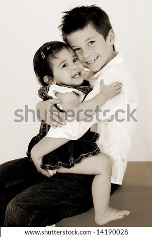 adorable brother & sister having hugs - stock photo