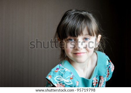 Adorable brunette child girl in colorful dress on dark background - stock photo