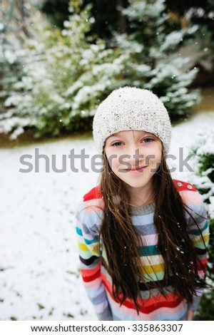 Adorable brunette kid girl with long hair in colorful sweater dress plays outdoor in snowfall - stock photo