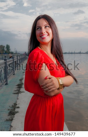 Adorable brunette Smiling with red dress posing on a dawn looking away. Fashion Beauty. Outdoors shot near river - stock photo