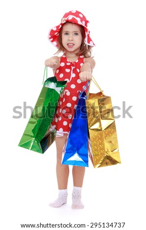 Adorable Caucasian little girl in a red short dress in polka dots with a red hat holding a front of a colorful shopping bags , the girl goes to do the shopping - isolated on white background - stock photo