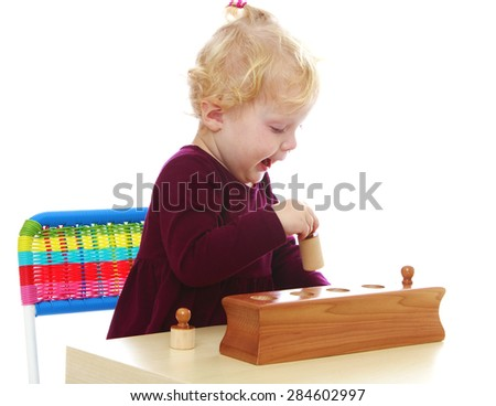 Adorable Caucasian little girl playing with Montessori material sitting at the table- isolated on white background - stock photo