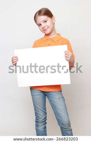 Adorable caucasian little girl with white blank for advertisment - stock photo