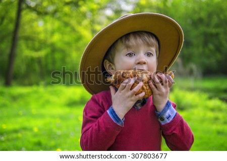 Adorable child biting into a croissant - stock photo