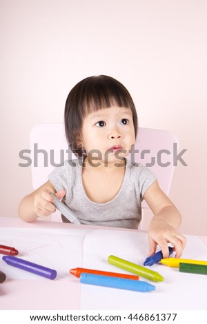 Adorable child drawing with colorful crayons and smiling, isolated on white - stock photo