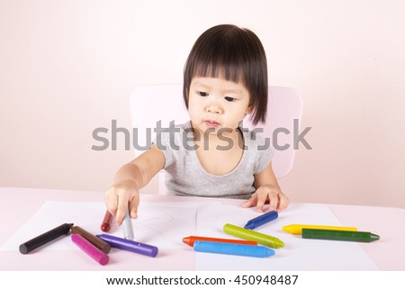 Adorable child drawing with colorful crayons and smiling, with the copy space. - stock photo