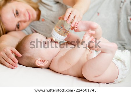 adorable child drinking from bottle. 5 months old girl. - stock photo