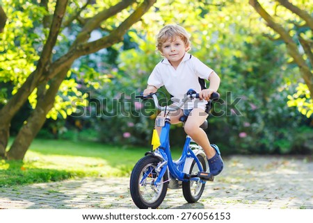 Adorable child having fun with riding his first bicycle on warm summer day. - stock photo