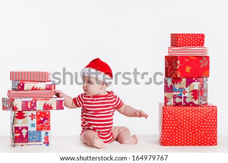Adorable child in santa cap with stacks of present boxes around sitting on the floor. Isolated on white background - stock photo