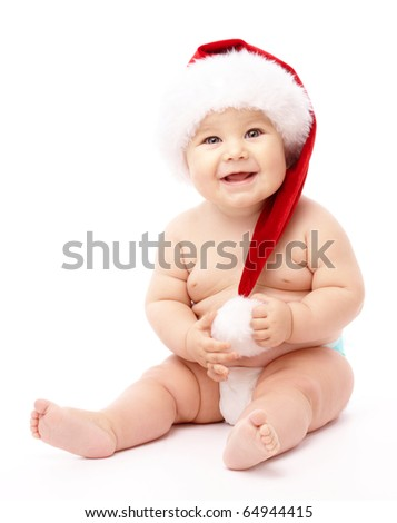 Adorable child is sitting on floor, wearing red Christmas cap, isolated over white - stock photo