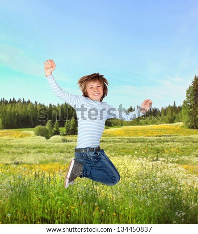 Adorable child jumping on the meadow with blue sky - stock photo