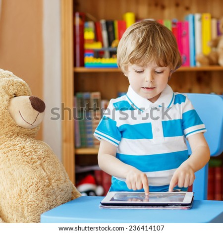 Adorable child playing with tablet computer in his room at home, indoors. - stock photo