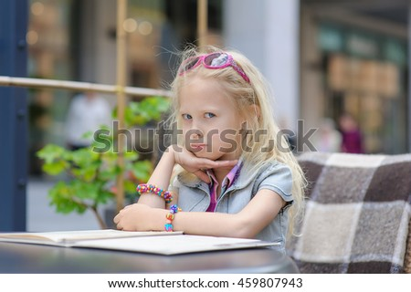 Adorable child reading menu in cafe. Toddler tired girl in beautiful outside cafe choosing meal from menu card. Shop windows in the background. Blond hair fluttering in the wind. - stock photo