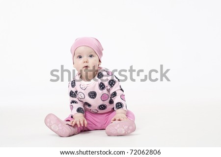 Adorable child sitting on the floor and looking at camera - stock photo