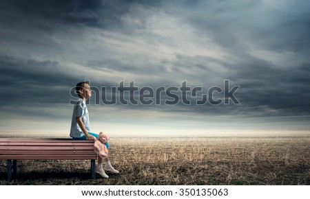Adorable child sitting on wooden bench with bear toy in hand - stock photo